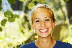 Smiling teenager shows off her dental crowns, also known as teeth crowns, available to patients in Spanish Springs and Reno.